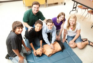 A group of teenage students learning CPR life saving techniques in class.